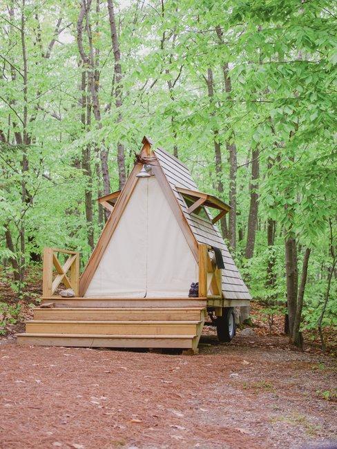 Verrijdbaar puntdak huisje met houten vlonder in bos