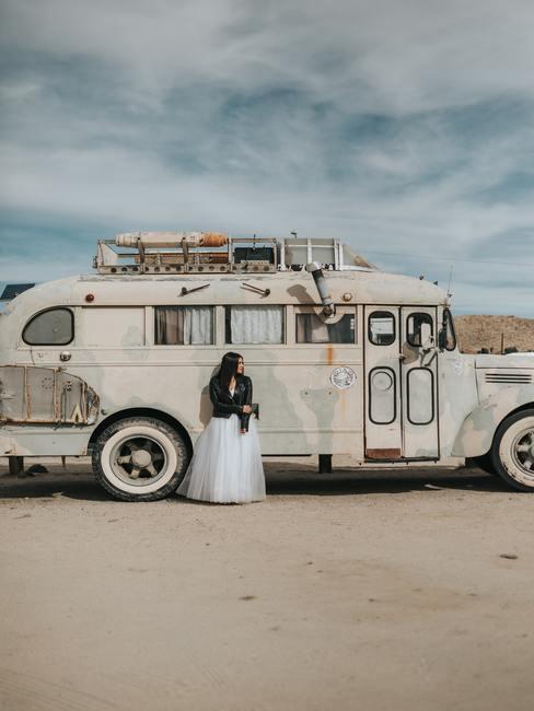 Oldtimer caravan met dame in witte rok in de woestijn