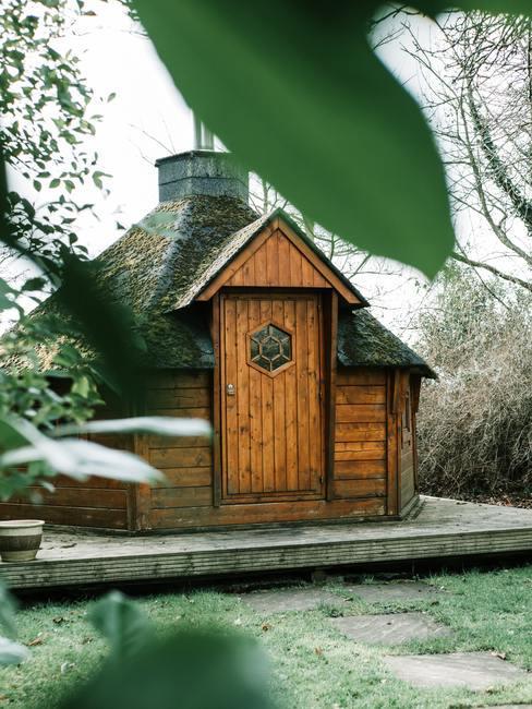Zes hoekig houten huis met schoorsteen en voordeur op houten verhoging in de natuur