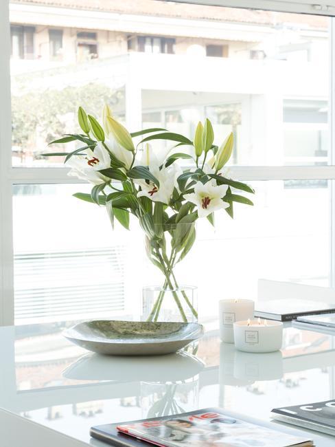 Witte tafel met bord, kaarsen en transparante vaas met lelies voor een raam