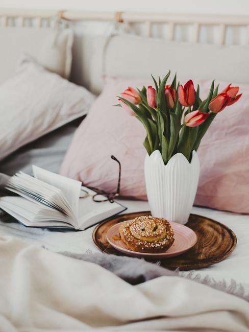 Tulpen in witte vaas met broodje op dienblad op bed met boek en bril ernaast