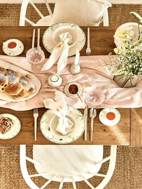 Tafelsetting van bonve gefotografeerd houten tafel met witte stoelen en vloerkleed