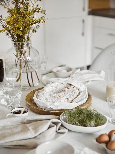 Gedekte tafel met paasbrood op houten plank en gedroogde bloemen in vaas
