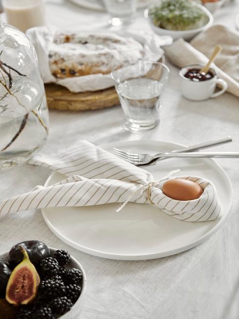 Gedekte tafel met wit tafellaken en wit bord en paashaas met ei ingezoomd op voorgrond
