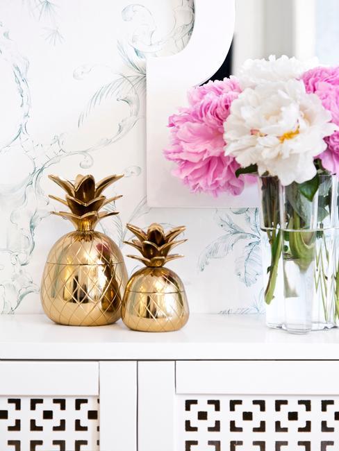 Decoratieve gouden ananas en bloemen in een vaas op de achtergrond van het behang met een patroon van wit-grijs marmer