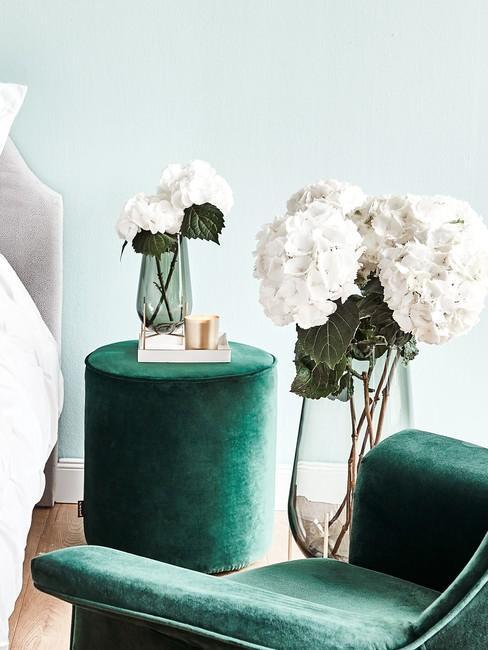 Lichtgroene muur met smaragdgroen poef en witte hortensia in vaas