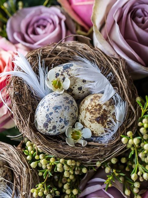 Nestje van takjes met gekleurde paaseieren in natuurtinten