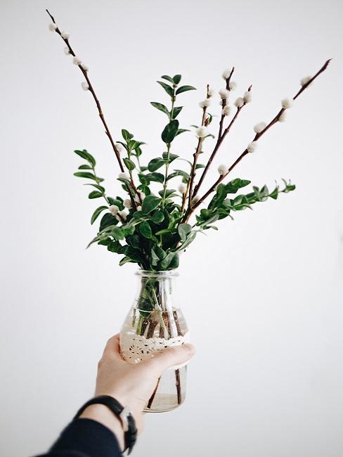 Tuindecoratie voor Pasen paastakken in een glas met hand