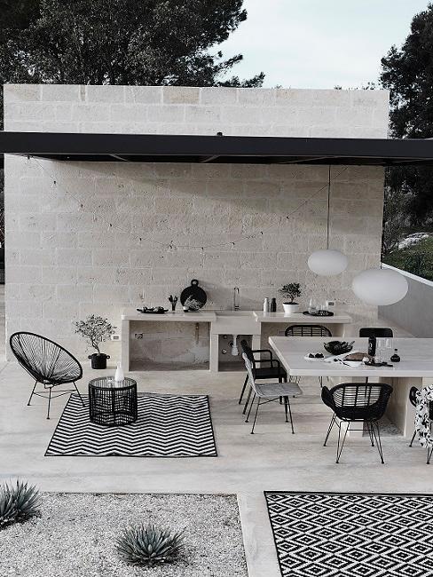 Grijze buitenkeuken met zwarte tuinstoelen en grijze tafel met witte lampen