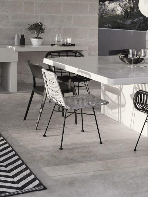 Buitenkeuken grijs met witte tafel en zwarte stoelen