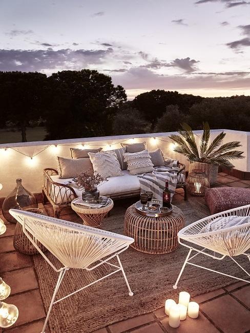 Dakterras in de avond met witte gevlochten stoelen in bohemian style