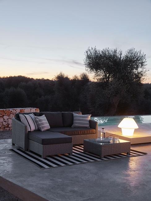 Avondsetting bij het zwembad met loungebank op gestreept vloerkleed
