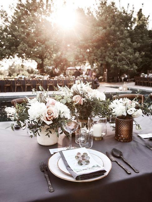 Bruiloft decoratie tafelsetting met bloemen bij ondergaande zon