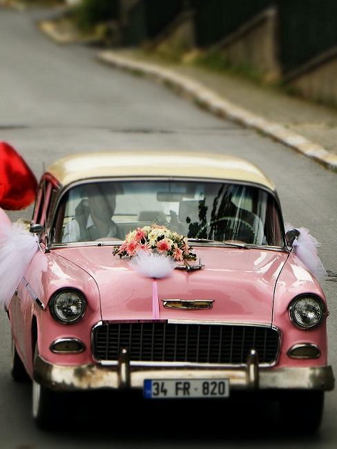 Bruiloft decoratie op een roze auto in boho stijl