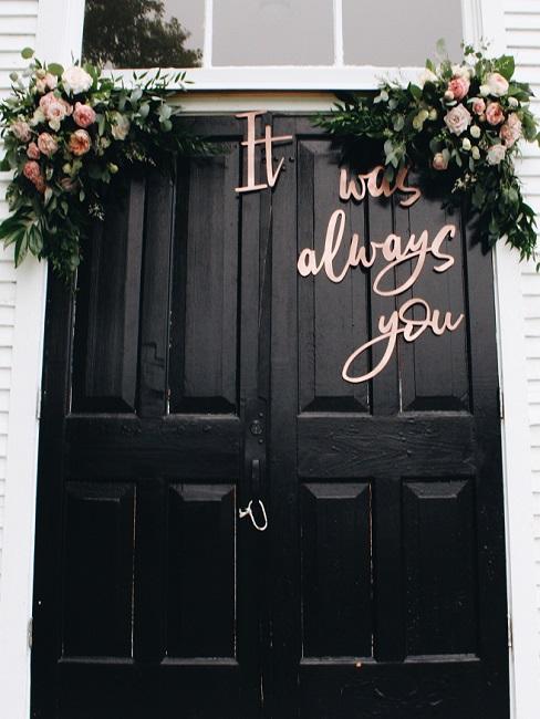 De opschrift op de zwarte monumentale deur met een bruiloft decoratie