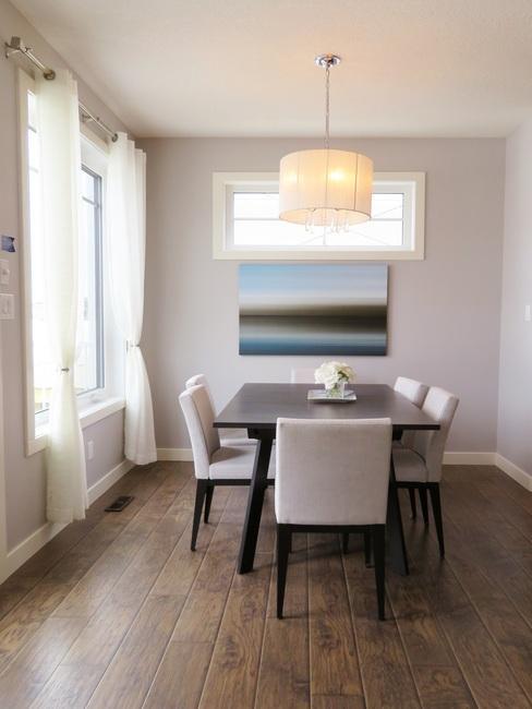 Woonkamer in een minimalistisch interieur met een donkerhouten tafel en witte stoelen en ingelijste print op een muur