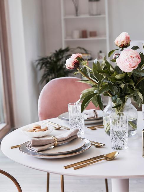 Romantisch interieur eettafel gedekt met pioenrozen