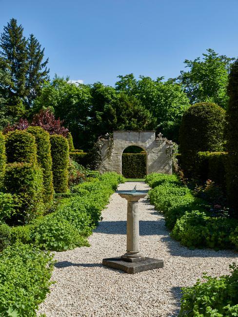 Feng shui tuin met water en fontijn op kiezelpad met stenen boog