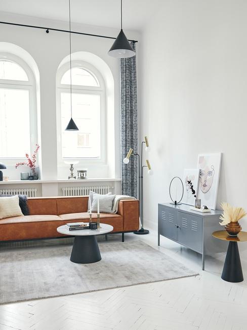 Suede schoonmaken: moderne woonkamer met leren zitbank, zwarte bijzettafel en grijze dressoir