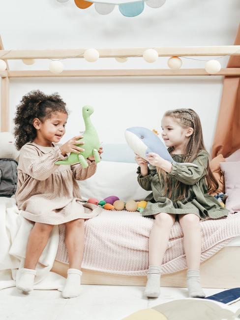 Meisjes spelen met speelgoed op het wit bed