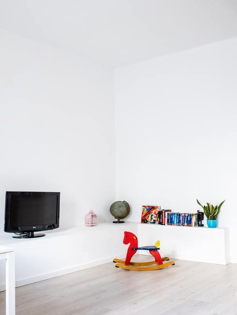 Rood schommelpaard in de kamer in het wit