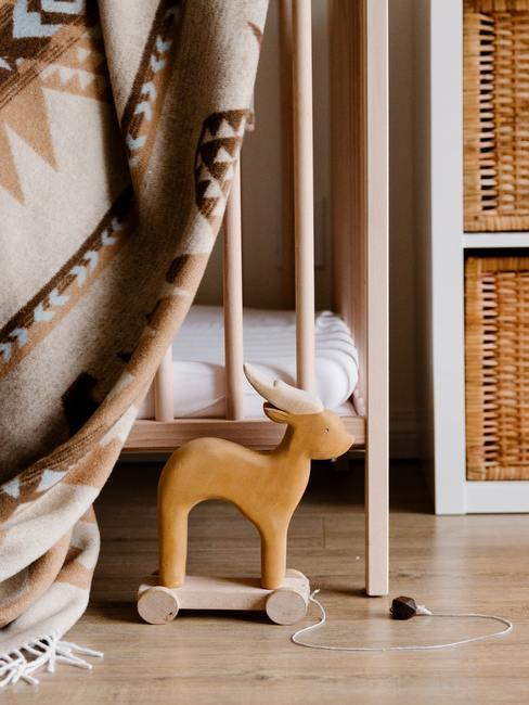 Babykamer hout: een houten speelgoed naast een wieg met wit linnen