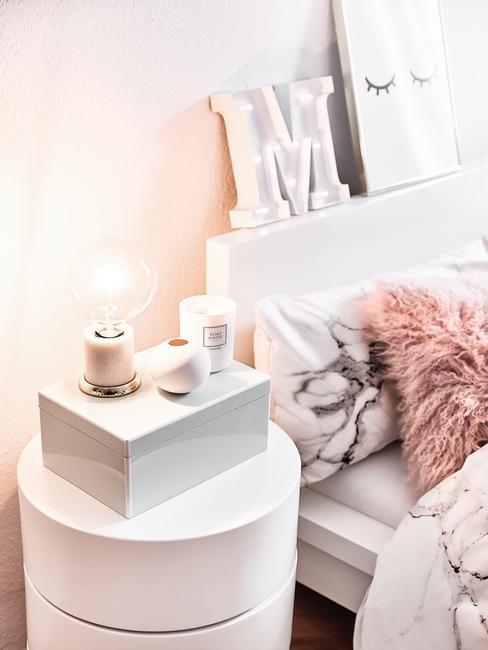Babykamer inspiratie: ouders bed met zachte kussens en wit nachtkastje met lamp en doos