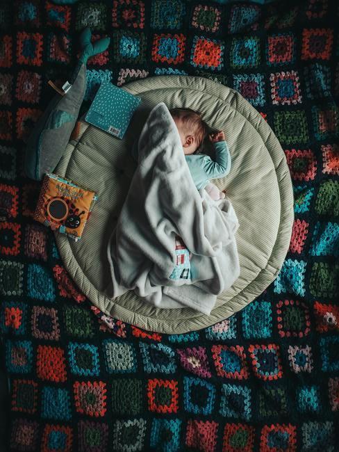 Baby liggend op de deken