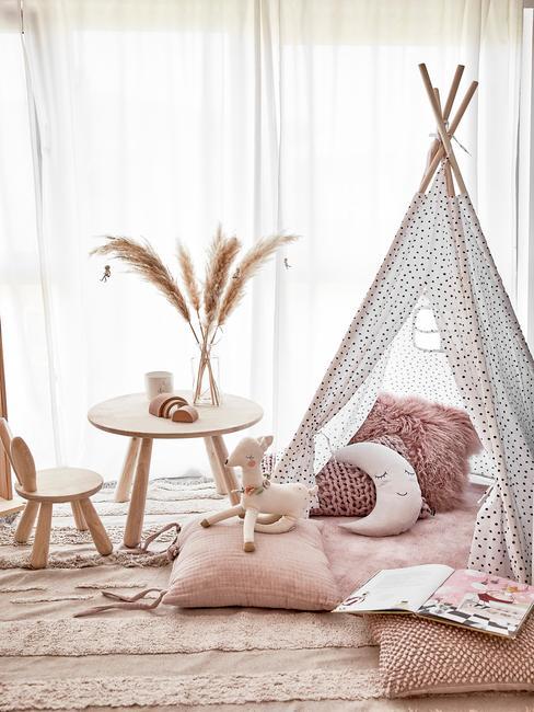 Tipi tent met zachte kussens en plaid in roze kleur naast een houten bijzettafel met vaas en geurkaars