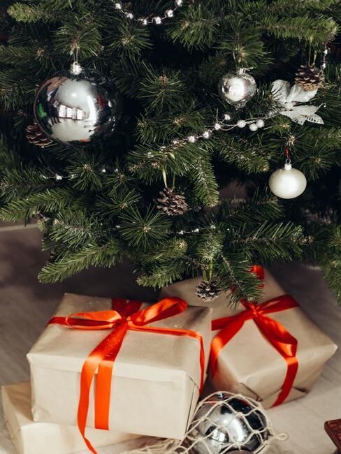 Cadeautjes onder de kerstboom gewikkeld in bruin papier met een rood lint