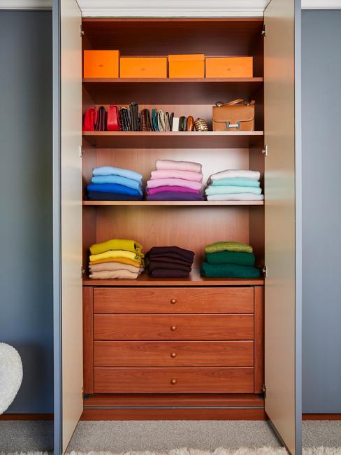 Szafa w pomieszczeniu wykonana z drewna z półkami na ubrania oraz szufladami