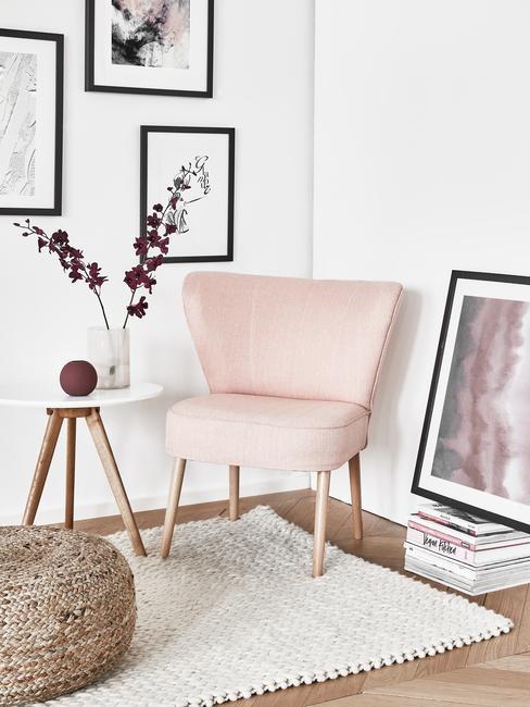 Różowy fotel, obok stolik z białym blatem. Na ścianie czarno-białe ilustracje