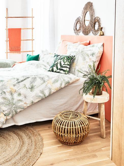 Sypialnia w stylu tropikalnym, z łożkiem o pomarańczowym zagłówku, zieloną pościelą oraz metalowymi dekoracjami ściennymi