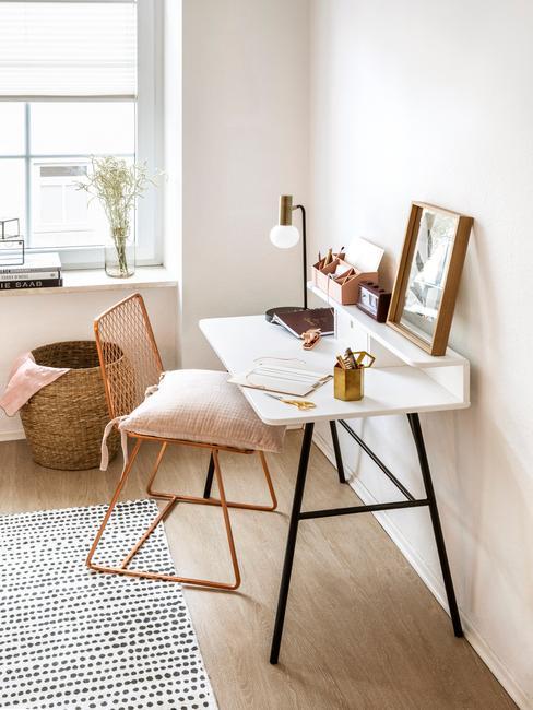 Fragment pokoju z białym biurkiem o czarnych nogach, krzesła z rattany i dywanu