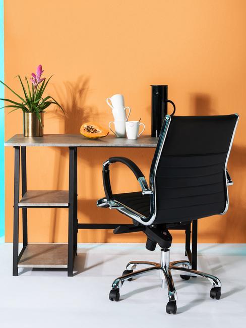 Pomarańczowy pokój z czarnym biurkiem oraz czarnym krzesłem biurowym
