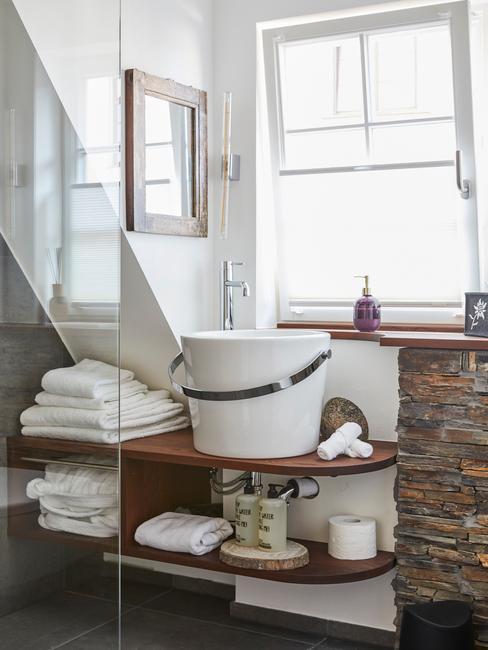 Fragment łazienki z okenm oraz drewnianymi półkami