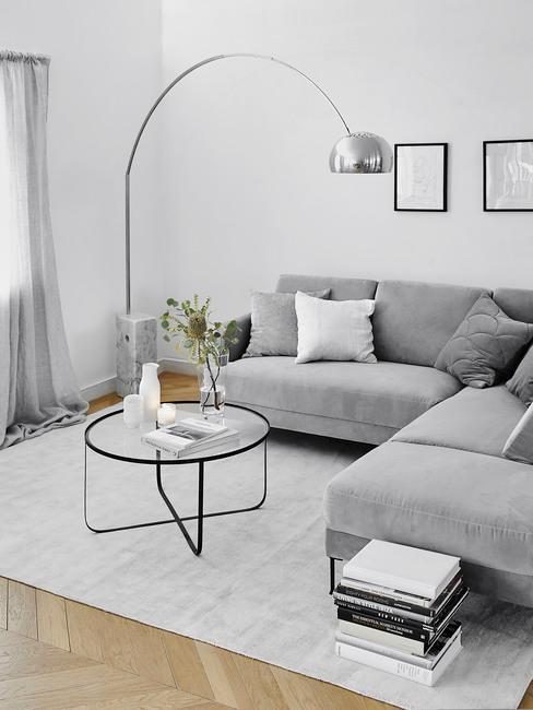Szara sofa i jasny dywan oraz lampa łukowa w stylu minimalistycznym