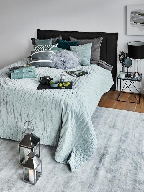 Sypialnia z turkusową pościelą, szarym dywanem oraz stolikiem nocnym