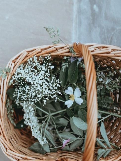 Koszyk wielkanocny z wikliny, w którym znajdują się kwiaty