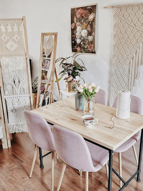 Salon z drewnianym stołem i pudrowo-różowymi krzesłami. Na ścianie makrama oraz makramowy parawan