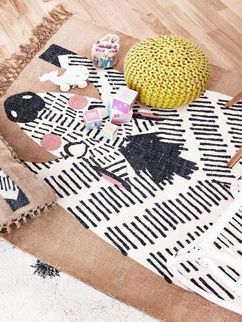 Dywan z zebrę w pokoju dziecięcy, na któym znajdują się zabawki