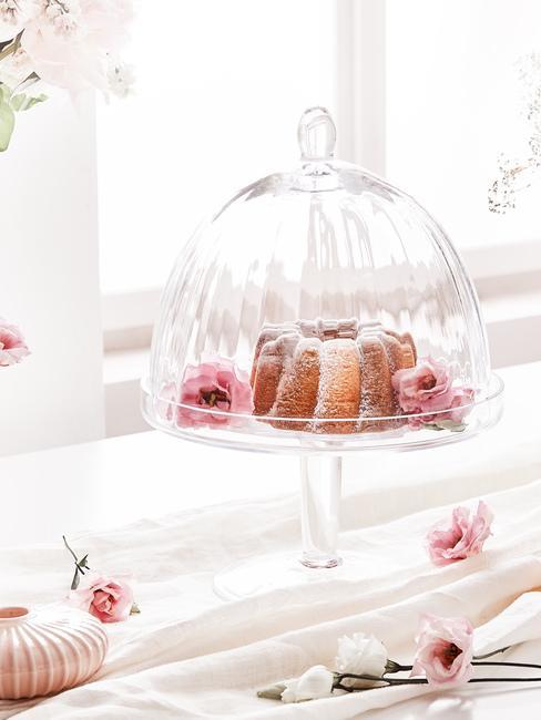 Szklana patera z ciastem oraz kwiatami ustawiona na parapecie przy oknie