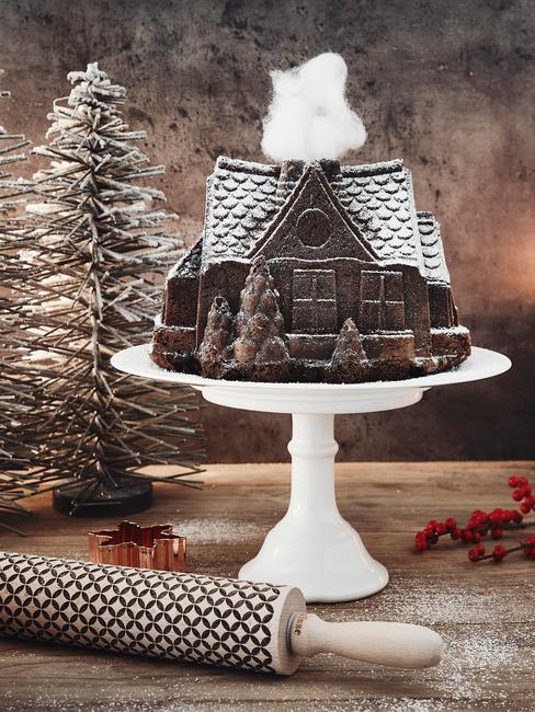 Biała patera z domkiem z pierwnika oraz dekoracjami świątecznymi