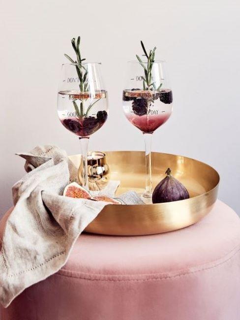 Dwa, szklane kieliszki z drinkami ustawione na złotej tacy, która jest położona na różowym pufie