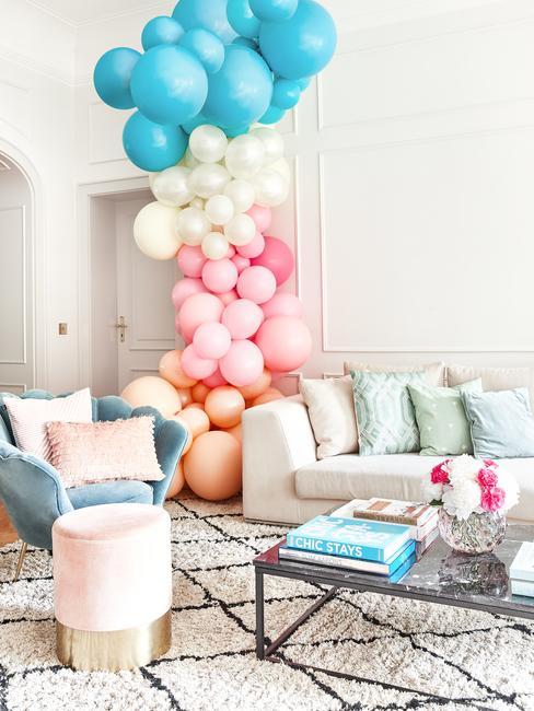 Jasny salon z sofą, fotelem oraz pufem udekorowany wieżą z balonów