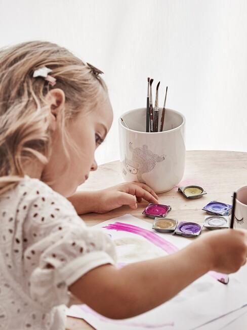 Dziewczynka malująca przy stole