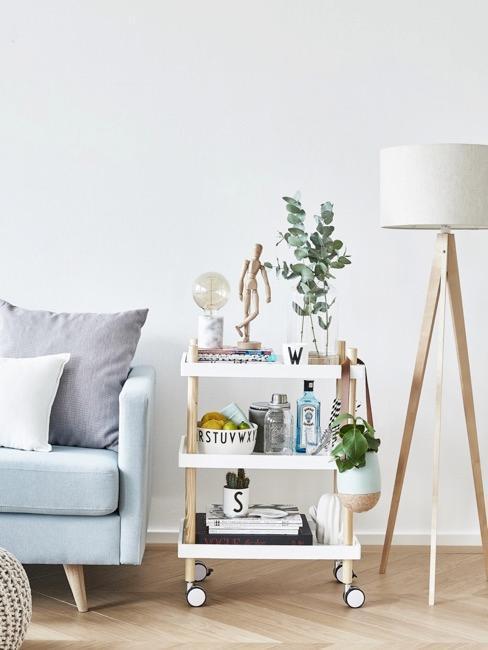 Fragment salonu z niebieską kanapą, białym wóżkiem barowym oraz lampą