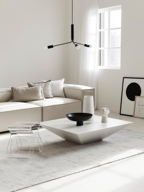 Jasny salon z biała sofą, białym stolikiem kawowym oraz dekoracjami