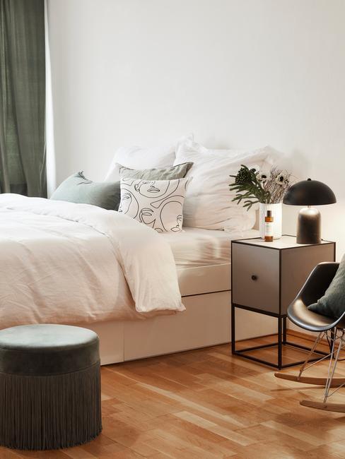 Biała sypialnia z dużym łożkiem z białą pościelą z ciemnozielonymi akcentami