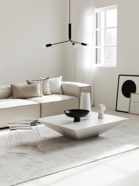 Jasny salon z sofą, stolikiem oraz designerskimi ozdobami